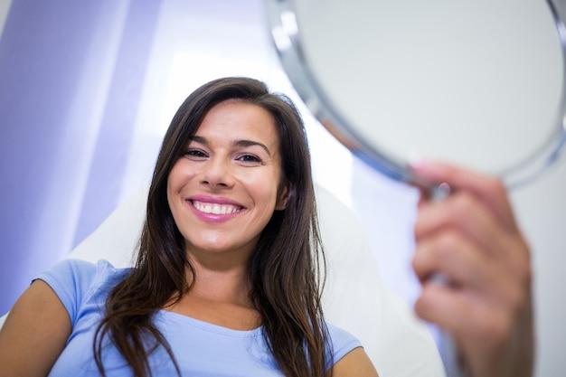 Paciente sorridente segurando um espelho na clínica Foto gratuita