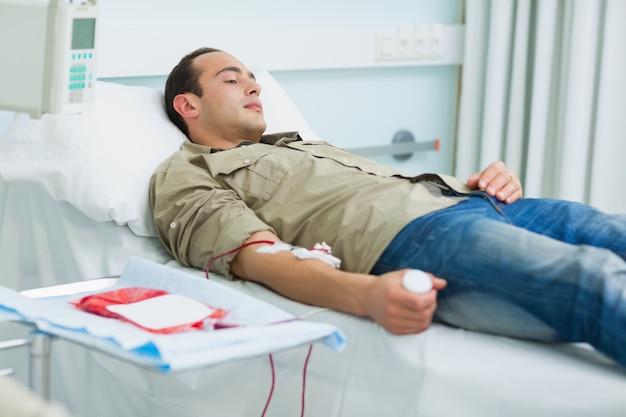 Paciente transfundido deitado em uma cama Foto Premium