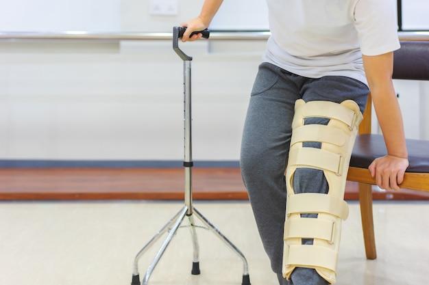 Pacientes do sexo feminino usam dispositivos de suporte de joelho para reduzir o movimento ao usar a bengala para se levantar da cadeira. Foto Premium