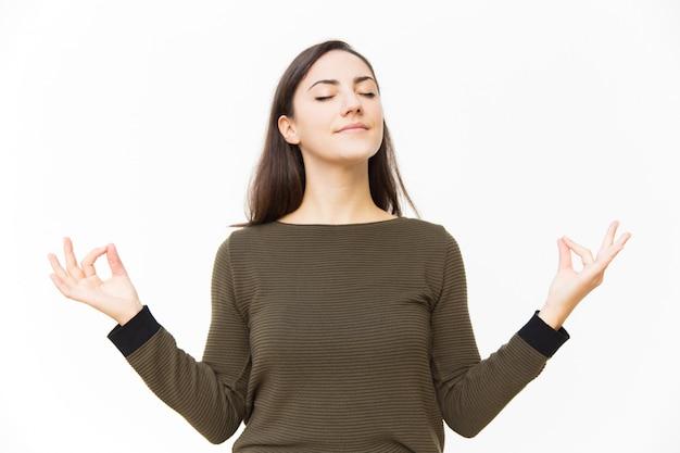 Pacífica mulher feminina tranquila, fazendo gesto de zen Foto gratuita