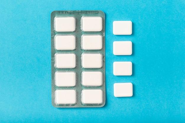Pacote de bolha de pastilha elástica branca sobre fundo azul Foto gratuita