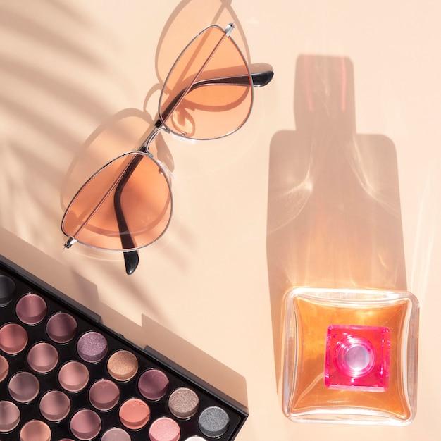 Pacote de cosméticos de beleza com perfume e óculos de sol Foto gratuita