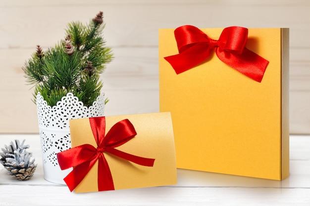 Pacote de natal de maquete e carta com um laço vermelho Foto Premium