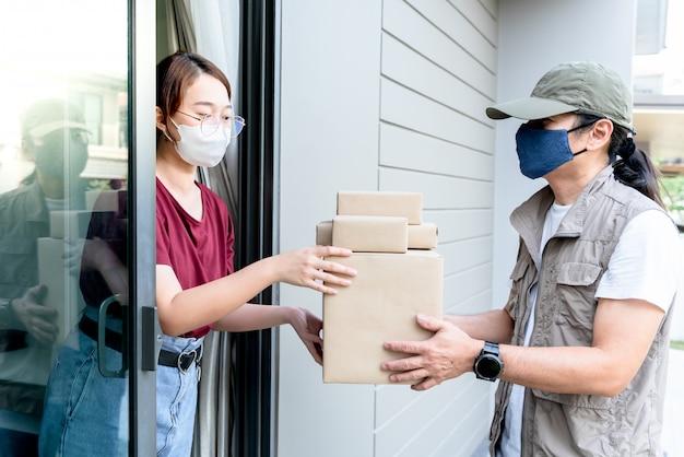 Pacote de recebimento de mulher do entregador, que ela encomendou produtos on-line Foto Premium
