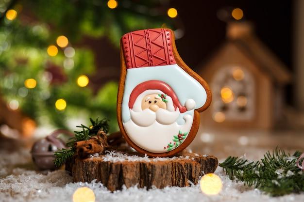 Padaria de comida tradicional de férias. luva de gengibre papai noel em decoração aconchegante e quente com luzes de guirlanda Foto Premium