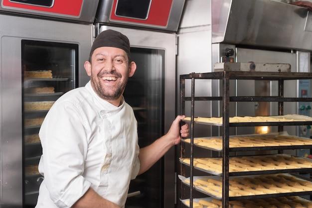 Padeiro de sorriso que põe uma cremalheira das pastelarias no forno na padaria ou na loja de pastelaria. Foto Premium