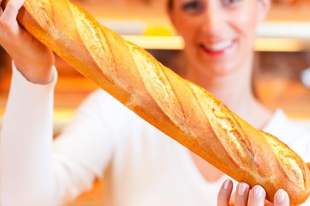 Padeiro feminino em sua padaria com baguete Foto Premium
