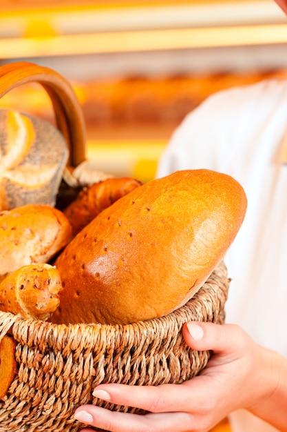 Padeiro feminino na padaria vendendo pão por cesta Foto Premium