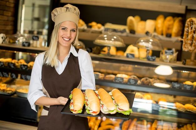 Padeiro feminino posando com vários tipos de sanduíches na padaria Foto Premium
