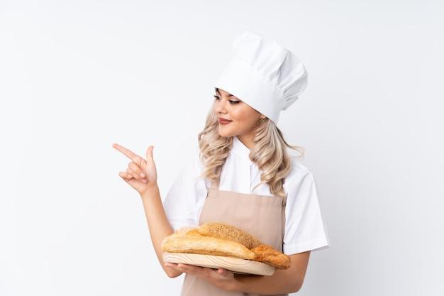 Padeiro feminino segurando uma mesa com vários pães sobre fundo branco isolado, apontando o dedo para o lado Foto Premium