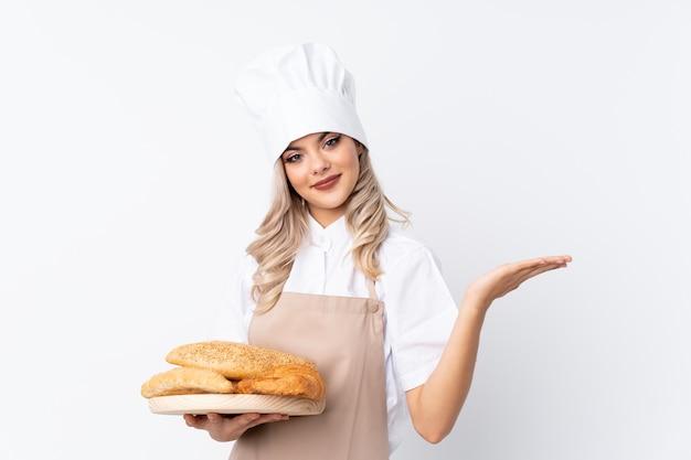 Padeiro feminino segurando uma mesa com vários pães sobre fundo branco isolado, segurando copyspace imaginário na palma da mão Foto Premium