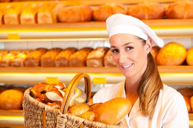 Padeiro feminino vendendo pão por cesto na padaria Foto Premium