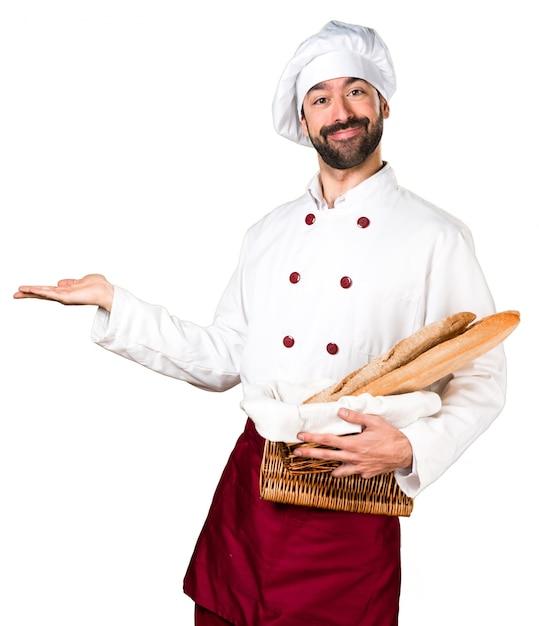 Padeiro jovem segurando um pouco de pão e apresentando algo Foto gratuita
