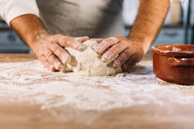 Padeiro masculino amassar farinha de massa na mesa de madeira Foto gratuita