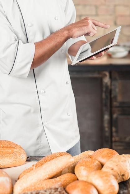 Padeiro masculino em pé atrás da mesa com pães usando tablet digital Foto gratuita