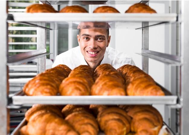 Padeiro masculino em pé atrás das prateleiras cheios de croissant fresco assado Foto gratuita