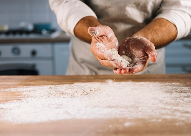 Padeiro masculino polvilhado na mesa de madeira com farinha de trigo Foto gratuita
