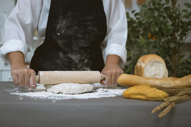 Padeiro masculino prepara pão com farinha Foto gratuita