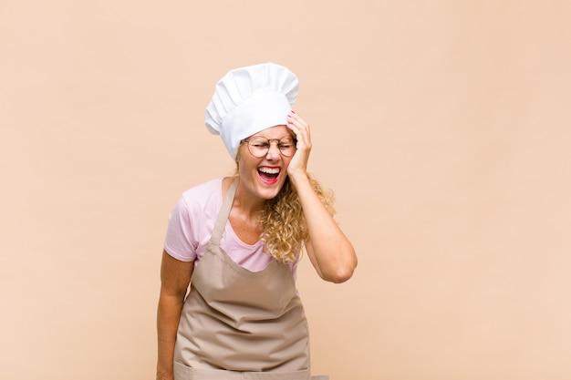 Padeiro mulher de meia-idade rindo e batendo na testa como dizer oh! eu esqueci ou isso foi um erro estúpido Foto Premium