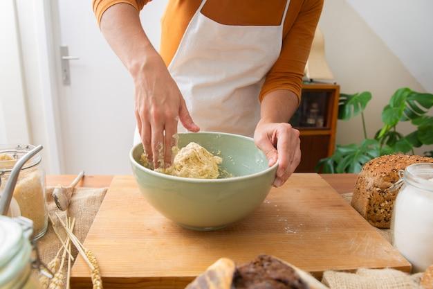 Padeiro no avental amassar massa para massa e pão saboroso Foto gratuita