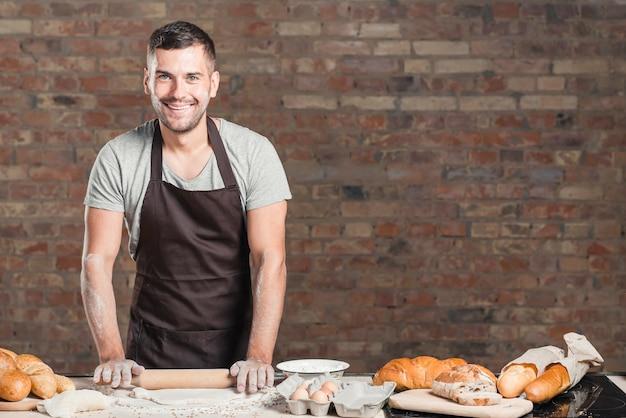 Padeiro sorridente achatando a massa com o rolo na bancada da cozinha Foto gratuita
