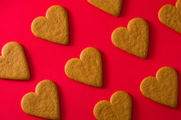 Padrão de biscoitos em forma de coração na superfície vermelha Foto Premium