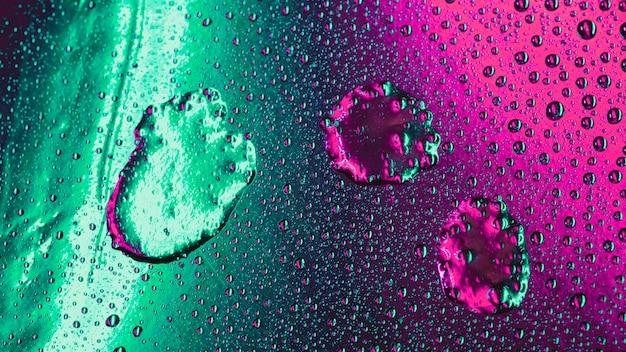 Padrão de bolhas no cenário de superfície verde e rosa molhado Foto gratuita