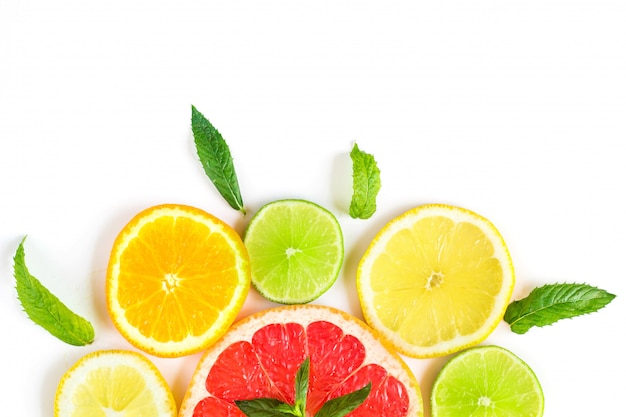 Padrão de comida cítrica no fundo branco - frutas cítricas sortidas com folhas de hortelã Foto Premium