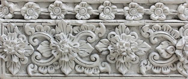 Padrão de flor cinza esculpida em design de estuque de parede nativa Foto Premium