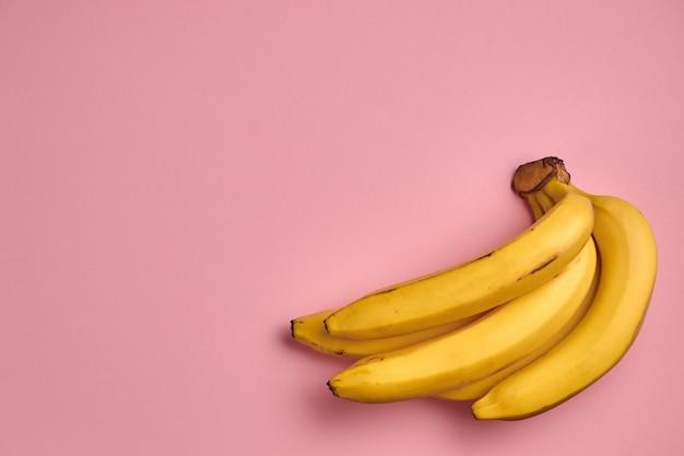 Padrão de fruta colorida de bananas amarelas frescas na rosa Foto Premium
