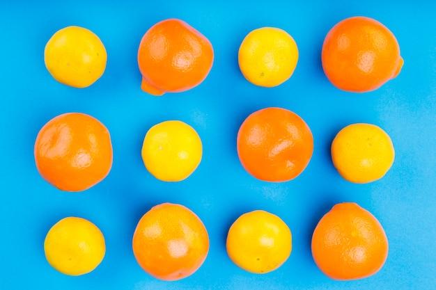Padrão de laranjas inteiras no pano de fundo azul Foto gratuita
