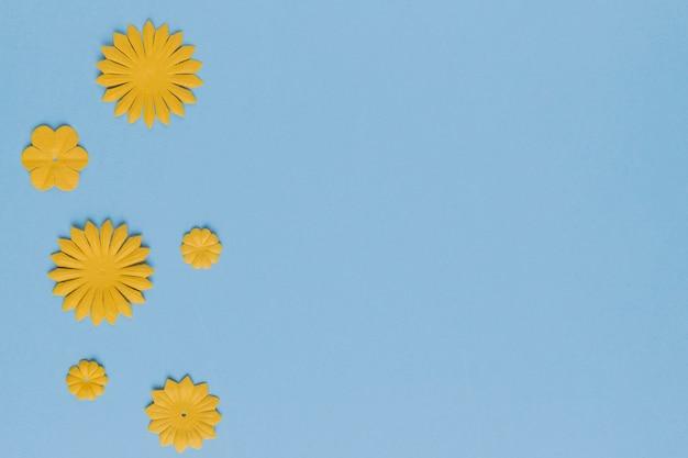 Padrão diferente de recorte de flor amarela sobre fundo azul Foto gratuita
