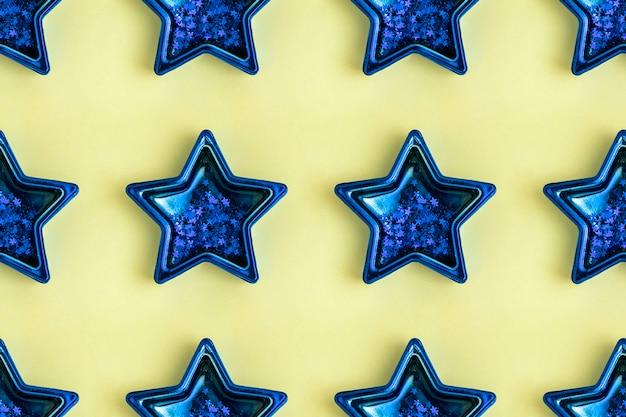 Padrão sem emenda de estrela metálica azul de cinco pontas na superfície amarela. decoração brilhante. Foto Premium