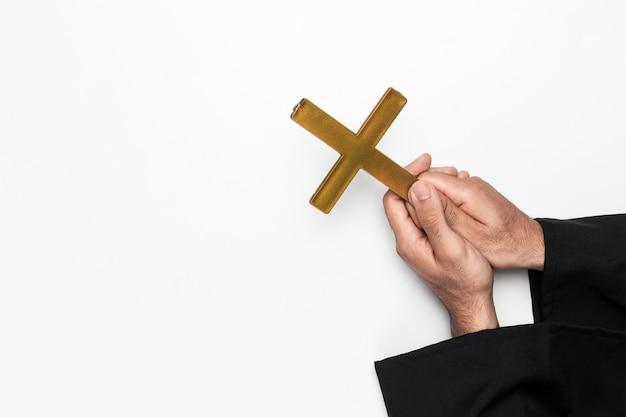 Padre segurando a cruz sagrada nas mãos Foto gratuita