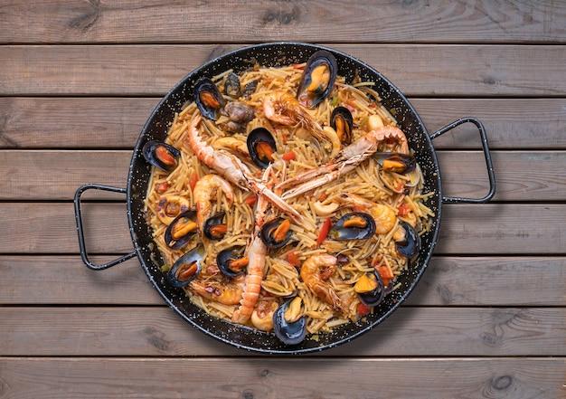 Paella de massa de frutos do mar, culinária espanhola em fundo de madeira, vista superior Foto Premium