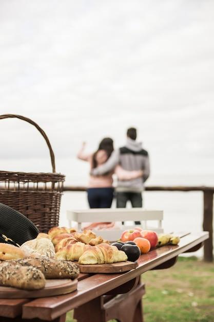 Pães e frutas assadas na mesa de madeira e casal no fundo Foto gratuita
