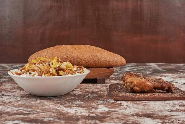 Pãezinhos de pão com uma tigela de macarrão e coxas de frango. Foto gratuita