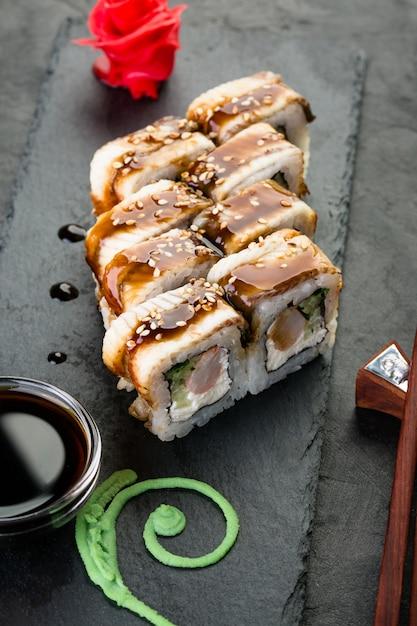 Pãezinhos e sushi em um fundo preto ardósia, cozinha japonesa Foto Premium