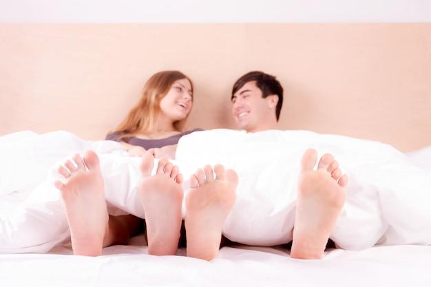 Paga de feliz casal jovem apaixonado em casa na cama de manhã. casal se divertindo. Foto Premium