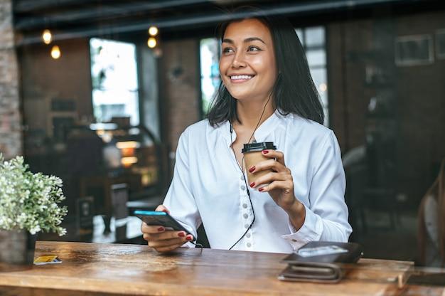 Pagar café com cartão de crédito através de um smartphone no café Foto gratuita