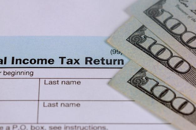 Pagar imposto conceito eua formulário de imposto 1040 com 100 notas de dólar dos eua. Foto Premium