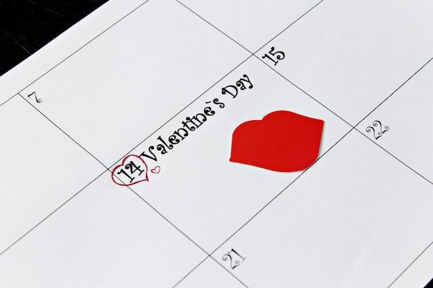 Página de calendário com os lábios em 14 de fevereiro, dia dos namorados em um fundo preto. Foto Premium
