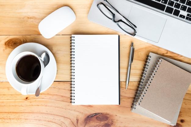 Página do caderno em branco está no topo da mesa de mesa de escritório de madeira com suprimentos em lay plana. Foto Premium