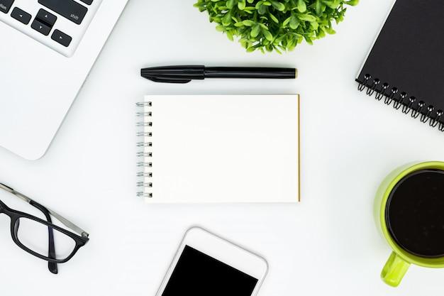Página do caderno em branco no meio da mesa de mesa de escritório branco. vista superior, lay plana. Foto Premium