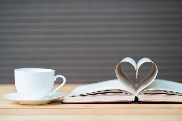 Página do livro forma de coração curvo e xícara de café Foto Premium