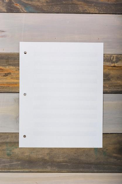 Página musical branca em branco presa na parede de madeira Foto gratuita