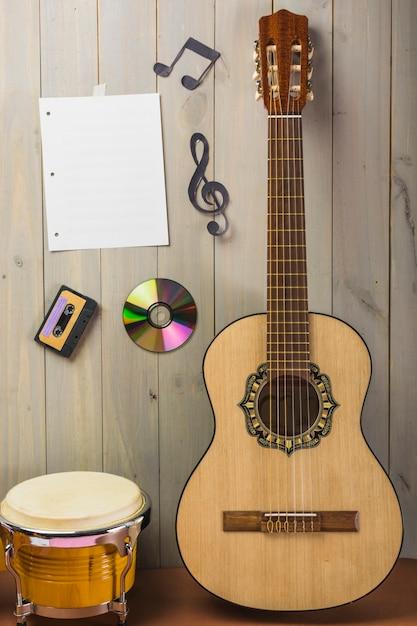 Página musical em branco; cassete; disco compacto; e nota musical preso na parede de madeira com guitarra e bongô Foto gratuita