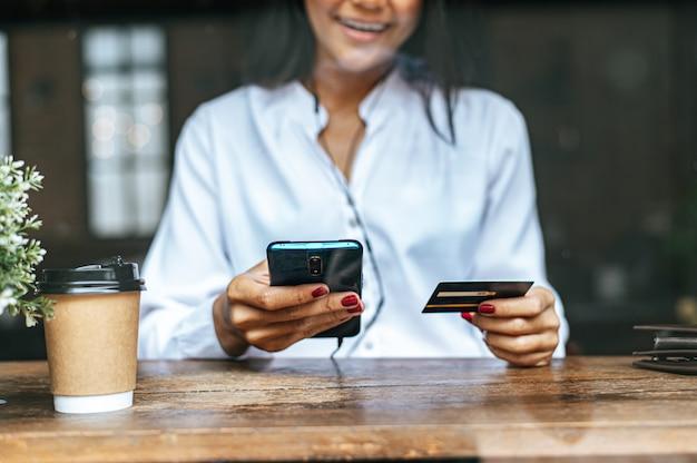 Pague as mercadorias com cartão de crédito através de um smartphone em uma cafeteria. Foto gratuita