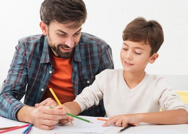 Pai ajudando filho com lição de casa Foto gratuita