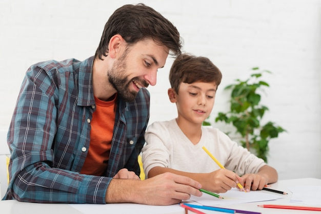 Pai ajudando o filho pequeno com lição de casa Foto gratuita